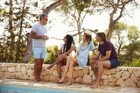 couples outdoors: Two adult couples socialising outdoors by a swimming pool Stock Photo