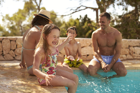 Family On Vacation Having Fun By Outdoor Pool