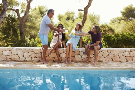 couples outdoors: Two couples socialising by a pool outdoors make a toast