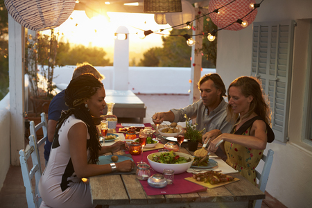 Two couples eating dinner at a table on a rooftop terrace