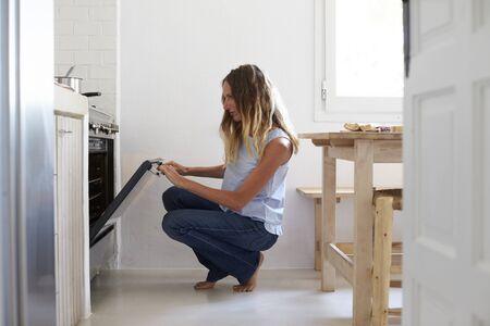 en cuclillas: Mujer en cuclillas en la cocina para mirar en el horno
