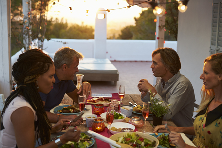 dining out: Two couples eating dinner on a roof terrace, close up