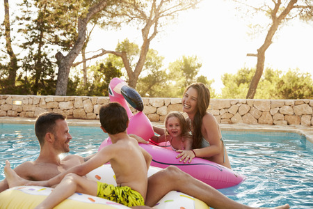 resting: Family On Vacation On Inflatables In Outdoor Swimming Pool Stock Photo