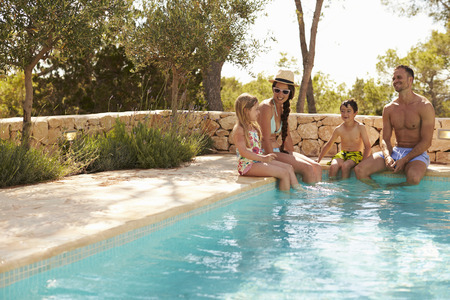 Wide Angle View Of Family On Vacation Relaxing By Pool