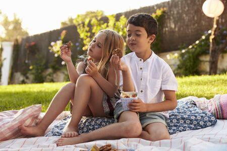 Twee kinderen die van Picknick op Deken in Tuin genieten
