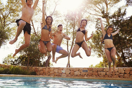 Teenagers jumping into an outdoor pool look to camera, Ibiza Stock Photo