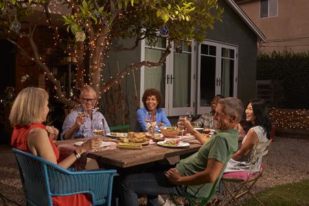 뒷마당에서 야외 식사를 즐기고있는 성숙한 친구의 그룹