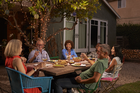 Group Of Mature Friends Enjoying Outdoor Meal In Backyard Imagens - 77956323