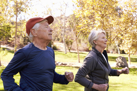 Side View Of Senior Couple Power Walking Through Park