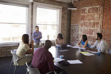 addressing: Businessman Standing To Address Boardroom Meeting Stock Photo