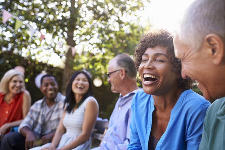 裏庭で一緒に社会的ニすることの成長した友人のグループ 写真素材