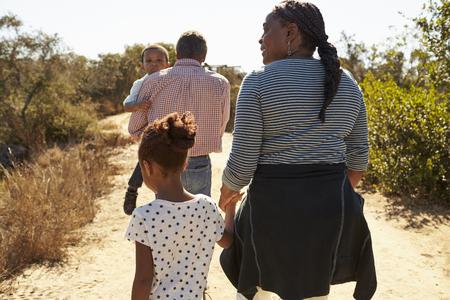 Großeltern und Enkelkinder gehen zusammen in die Landschaft