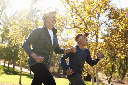 Side View Of Senior Couple Power Walking Through Park Reklamní fotografie