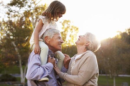 Grootouders geven kleindochter een schouderrit in Park Stockfoto