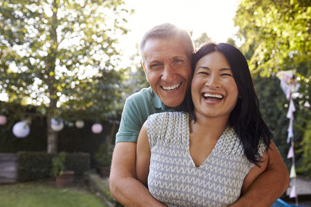 Portrait Of Loving Mature Couple In Back Yard Garden Stock Photo - 77969744
