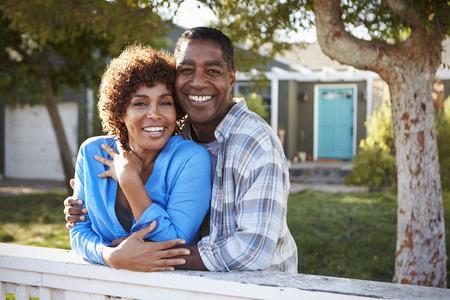 裏庭のフェンスを越えて探している成熟したカップルの肖像画 写真素材