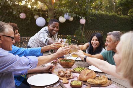 Grupo de amigos maduros disfrutando de comida al aire libre en el patio de campo Foto de archivo - 77934483