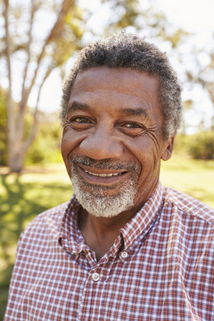Outdoor Head And Shoulders Portrait Of Mature Man In Park Stock Photo