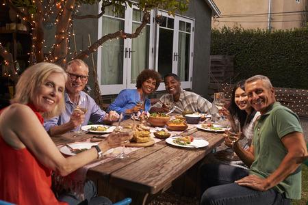 Porträt von den reifen Freunden, die Mahlzeit im Freien im Hinterhof genießen
