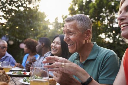 成熟した友人の家の裏庭の屋外の食事を楽しむ会