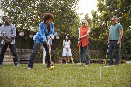 Group Of Mature Friends Playing Croquet In Backyard Together Standard-Bild