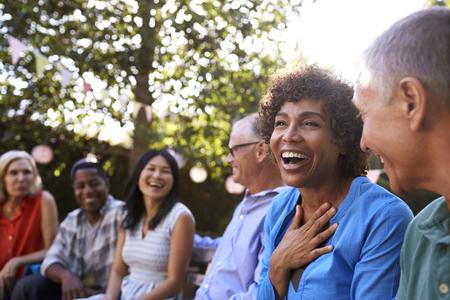 Group Of Mature Friends Socializing In Backyard Together Banco de Imagens - 77933176