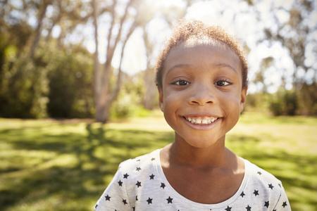 niños negros: Outdoor Head And Shoulders Shot Of Young Girl In Park Foto de archivo