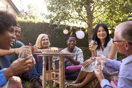 Gruppe von reifen Freunden genießen Getränke im Hinterhof zusammen