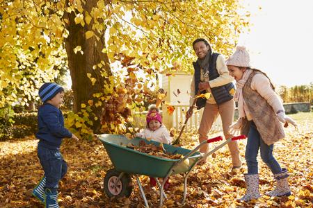 정원에서 가을 잎을 모으는 아이들을 돕는 아이들