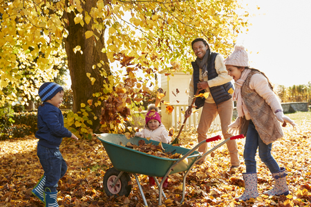 Children Helping Father To Collect Autumn Leaves In Garden
