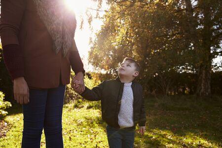 Boy Holding Mothers Hand On Autumn Walk in Garden