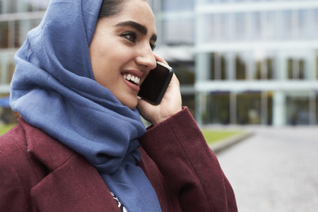 British Muslim Woman Using Mobile Phone Outside Office