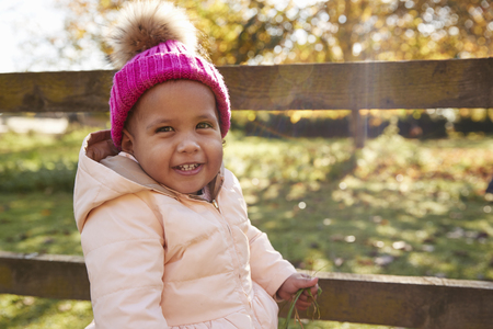 Young Girl On Autumn Walk Standing By Wooden Fence Stock Photo
