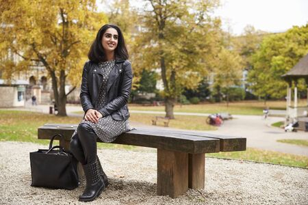 British Muslim Woman Sitting On Bench In Park