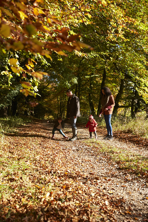 Family On Autumn Walk In Woodland Together
