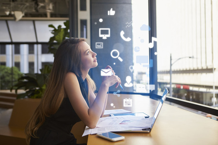 Businesswoman working in an office looking at app icons