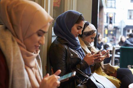コーヒー ショップの外のイギリスのイスラム教徒の女性のテキスト メッセージのグループ