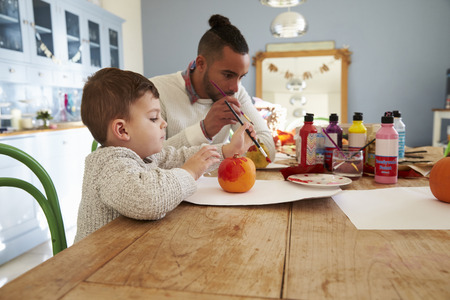 Father And Son Decorating Halloween Pumpkins At Home Stock Photo