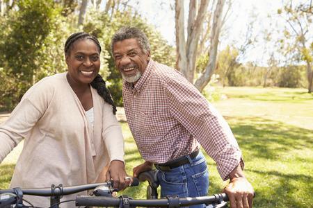 公園で自転車に乗るのために行く大人のカップルの肖像画