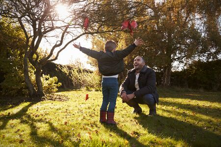 Boy And Father Playing With Autumn Leaves in Garden Stock Photo