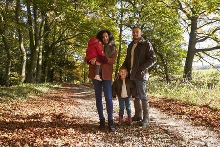front view: Portrait Of Family On Autumn Walk In Woodland Together Stock Photo
