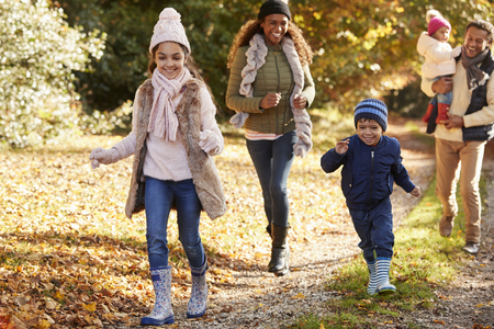 Family Running Along Path Through Autumn Countryside