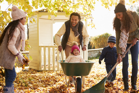 african american woman: Children Helping Parents To Collect Autumn Leaves In Garden