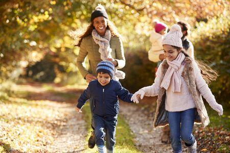 Family Running Along Path Through Autumn Countryside