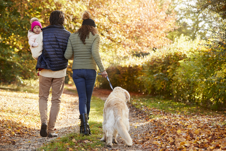 Family With Daughter And Dog Enjoy Autumn Countryside Walk