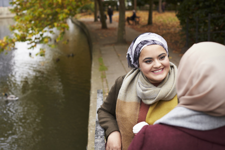 British Muslim Female Friends Talking By River In City