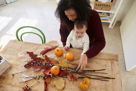 Mother And Daughter Making Autumn Decoration At Home