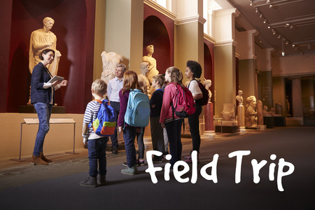 Uczniowie i nauczyciel na szkolnej wycieczce do muzeum z przewodnikiem