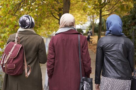 British Muslim Female Friends Walking In Urban Environment Stock Photo