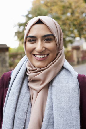 looking to camera: Portrait Of British Muslim Woman In Urban Environment Stock Photo